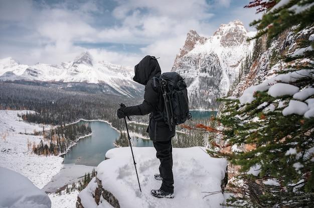 Fotograf mężczyzna stojący z kijkami trekkingowymi na śnieżnym szczycie z widokiem na góry i jezioro na płaskowyżu opabin w parku narodowym yoho, kanada