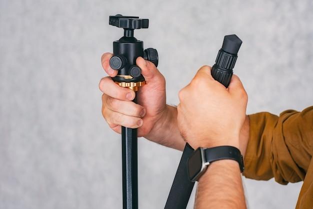 Fotograf mężczyzna trzyma w rękach profesjonalny statyw do robienia zdjęć i nagrywania filmów.