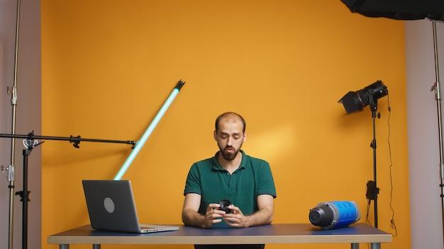 Fotograf nagrywa recenzję obiektywu technicznego dla subskrybentów vloga w studio. technologia obiektywu kamery cyfrowe nagrywanie twórca treści w mediach społecznościowych, profesjonalne studio do podcastów, vlogowania i