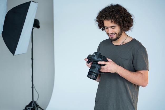 Fotograf oglądający zrobione zdjęcia swoim aparatem cyfrowym