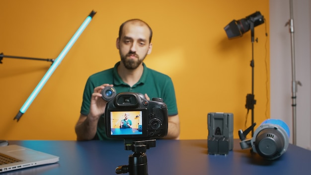 Fotograf opowiadający o specyfikacji obiektywu podczas nagrywania odcinka vloga dla subskrybentów. technologia obiektywu kamery cyfrowe nagrywanie twórca treści w mediach społecznościowych, profesjonalne studio dla po