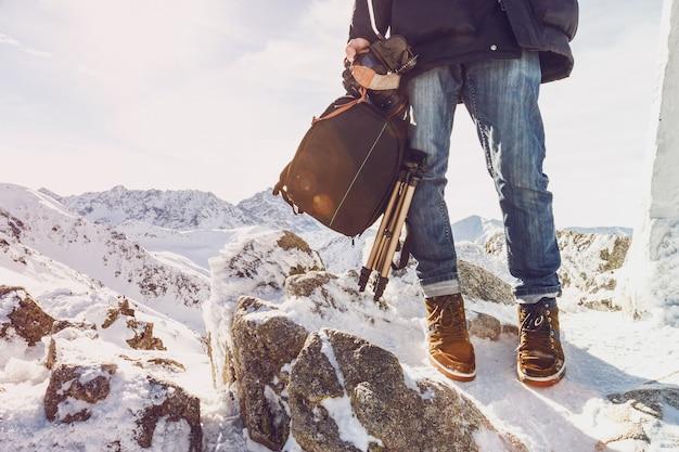 Fotograf podróżnik na szczycie góry z wyposażeniem w ręce