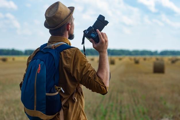 Fotograf podróżnik z aparatem w ręku na tle pola i stogów siana.