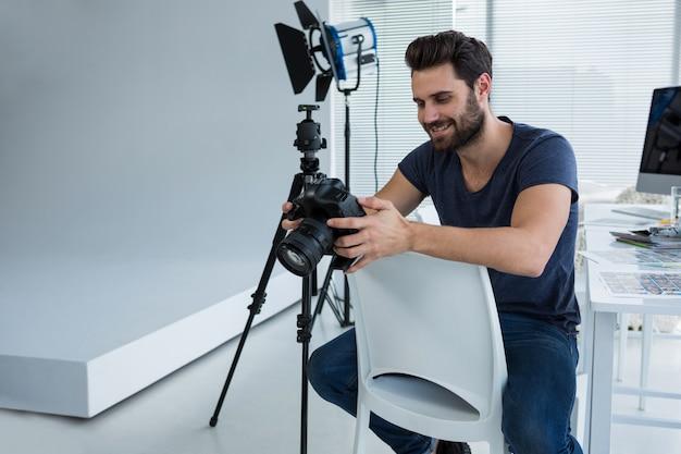 Fotograf przeglądający zrobione zdjęcia aparatem cyfrowym