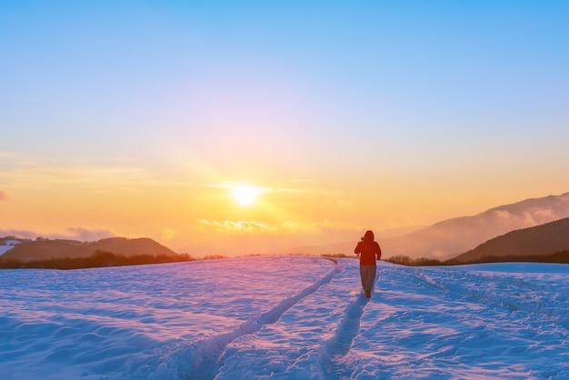 Fotograf przyrody na zaśnieżonym polu o zachodzie słońca