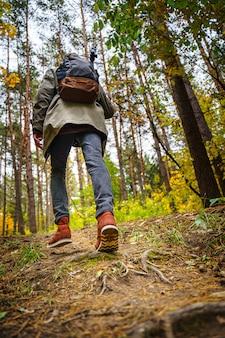 Fotograf przyrody ze statywem na ramieniu i plecakiem wspina się po zboczu w niesamowitym jesiennym lesie.