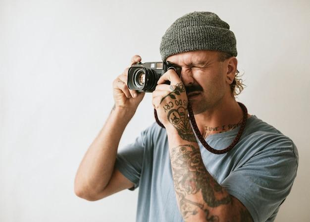 Fotograf pstrykający aparatem analogowym