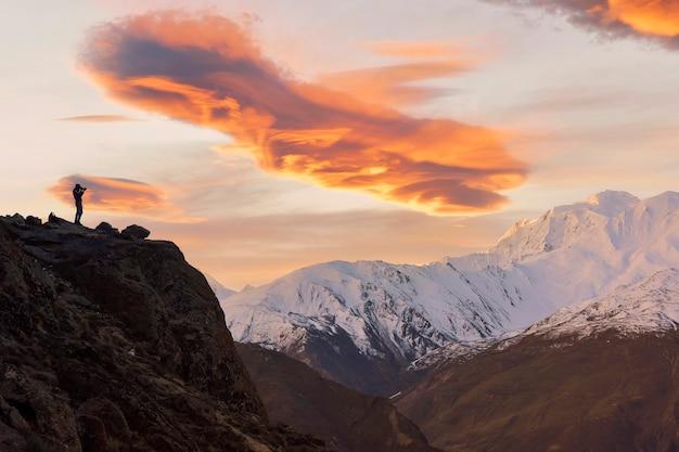 Fotograf robi zdjęcia na górze.sylwetka fotografa na szczycie góry