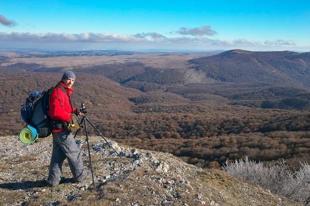 Fotograf robi zdjęcia na szczycie góry jesienią. podróżnik z plecakiem na szczycie góry