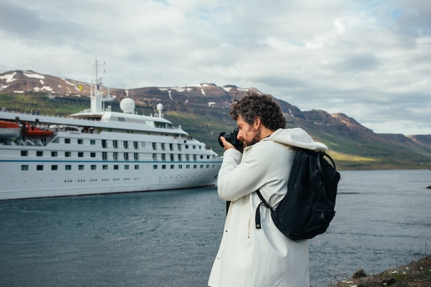 Fotograf robi zdjęcia statku wycieczkowego po fiordzie