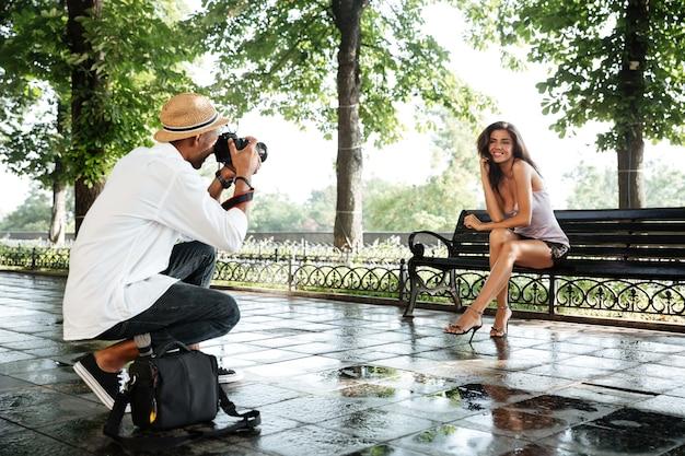 Fotograf robi zdjęcie młodej pięknej brunetki w parku