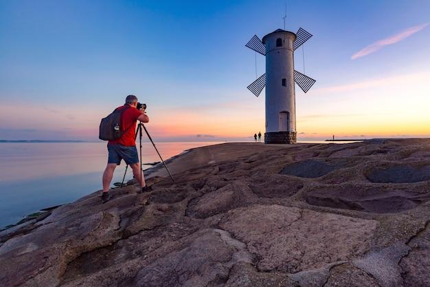 Fotograf robi zdjęcie stawy młyny o zachodzie słońca, oficjalnego symbolu świnoujścia, polska