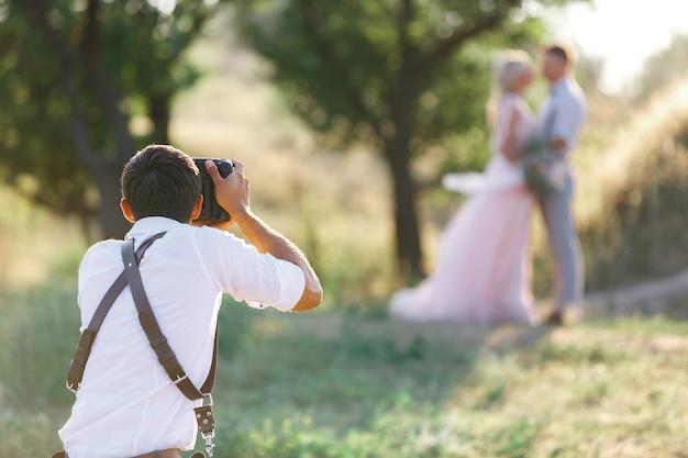 Fotograf ślubny robi zdjęcia młodej pary na łonie natury. para ślubna na sesję zdjęciową. fotograf w akcji