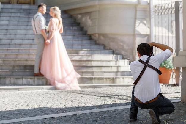 Fotograf ślubny robi zdjęcia młodej pary w mieście. para ślubna na sesję zdjęciową. fotograf w akcji