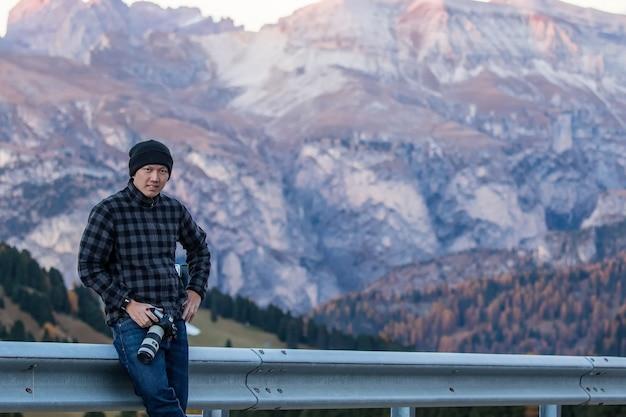 Fotograf stojący przy drodze i patrzący pod swoim kątem, aby zrobić zdjęcie w bolzano we włoszech.