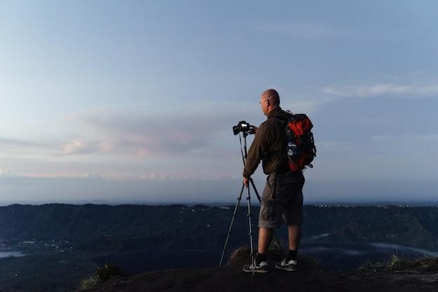 Fotograf turysta mocuje aparat na statywie do fotografii krajobrazowej