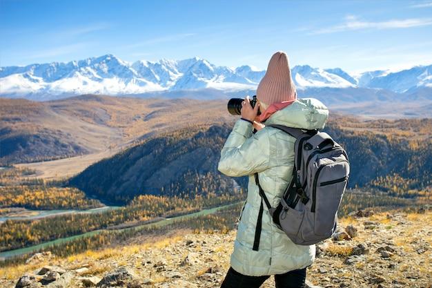 Fotograf turystyczny kobieta robi zdjęcia aparatem wideo lub fotograficznym krajobrazu przyrody w górach jesienią.