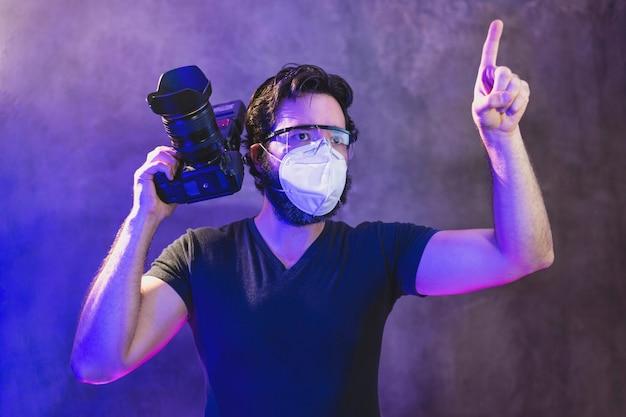 Fotograf w masce kn95 z profesjonalnym aparatem za kulisami produkcji wideo, koncepcja ochrony przed koronawirusem