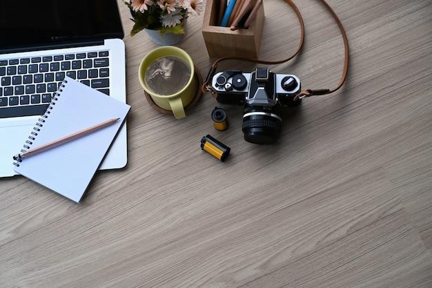 Fotograf w miejscu pracy z laptopa i kamery na drewnianym stole.