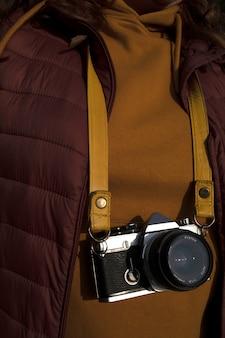 Fotograf w wiśniowym płaszczu i musztardowej koszulce z aparatem