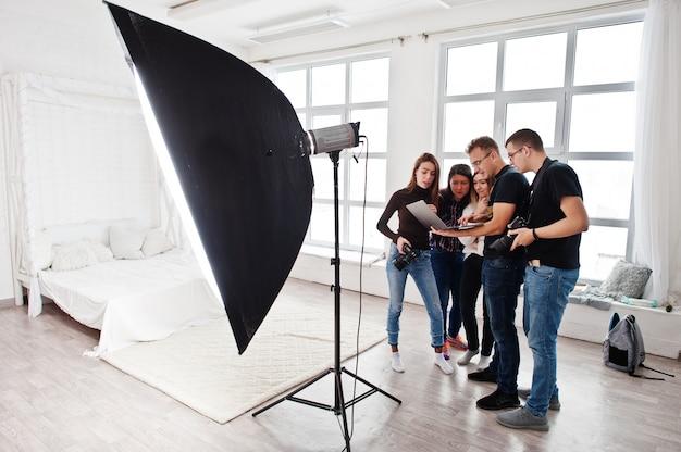 Fotograf wyjaśnia strzelanie do swojego zespołu w studio i patrzy na laptopa. rozmowa z asystentami trzymającymi aparat podczas sesji zdjęciowej. praca zespołowa i burza mózgów.