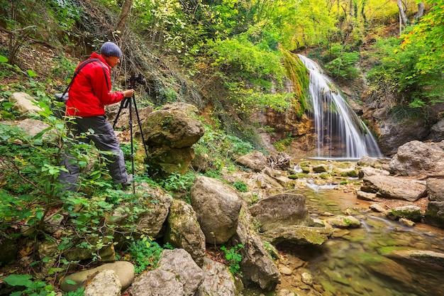 Fotograf wykonujący zdjęcia górskiego krajobrazu z wodospadem jesienią