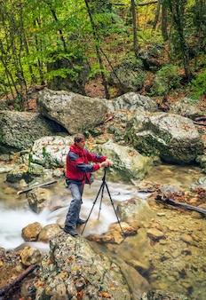 Fotograf wykonujący zdjęcia w górach z rzeką i wodospadem w okresie jesiennym