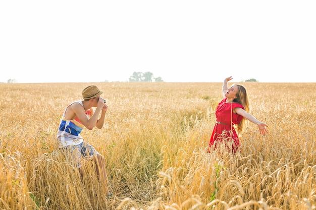 Fotograf z aparatem biorąc zdjęcie młodej pięknej kobiety w tej dziedzinie.