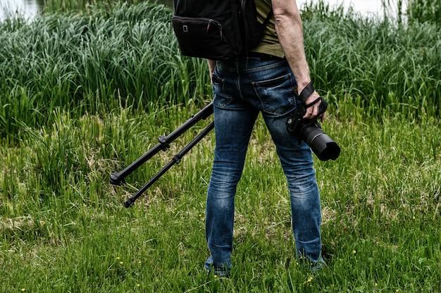 Fotograf z aparatem i statywem na tle miejskiego jeziora.