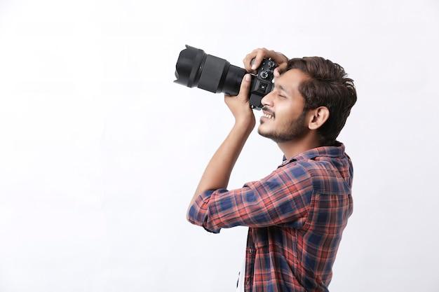 Fotograf z aparatem na białej ścianie