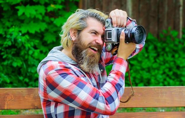 Fotograf z nowoczesnym aparatem cyfrowym. brodaty mężczyzna z profesjonalnym aparatem. koncepcja pracy zawodowej fotografii.