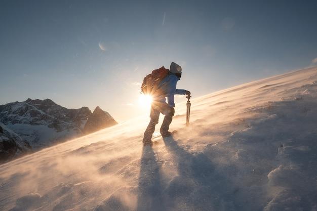 Fotograf ze statywem wspina się na zbocze wzgórza na górze ryten podczas zamieci o zachodzie słońca