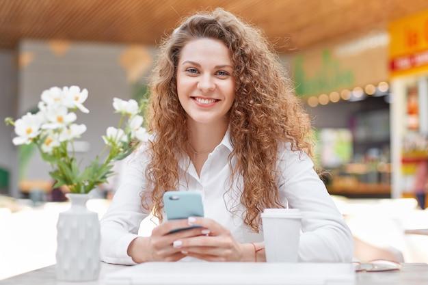 Fotografia atrakcyjna kędzierzawa kobieta z uśmiechem
