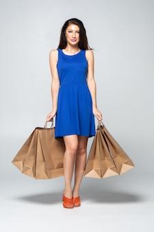 Fotografia atrakcyjna młoda kobieta trzyma up torba na zakupy odizolowywający