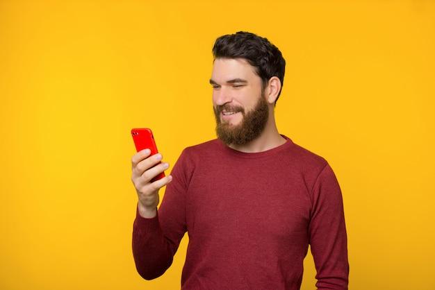 Fotografia brodaty facet w czerwonym pulowerze używać jego telefon komórkowego nad żółtym tłem