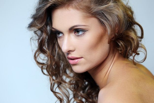 Fotografia brunetki dziewczyna z perfect skórą na szarym tle