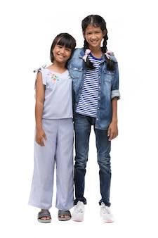 Fotografia dwa azjatykcia mała dziewczynka patrzeje kamerę z uśmiech twarzą.