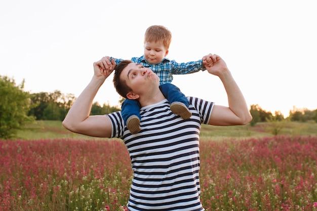 Fotografia dziecko całuje ojca obsiadanie na jego brać na swoje barki podczas gdy chodzący w polu przy zmierzchem