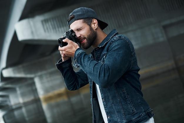 Fotografia hobby młody stylowy mężczyzna stojący na ulicy miasta, robiący zdjęcia w aparacie skoncentrowany