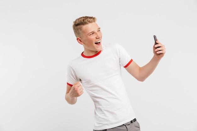 Fotografia jest ubranym przypadkową odzież krzyczy i zaciska pięść szczęśliwy młodzieniec jak zwycięzca podczas gdy trzymający telefon komórkowego odizolowywającego na bielu