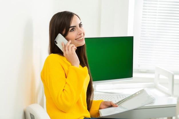 Fotografia kobieta w żółtym pulowerze pracuje od domu. kobieta rozmawia przez telefon i czyta dokumenty. opieka zdrowotna. zostać w domu