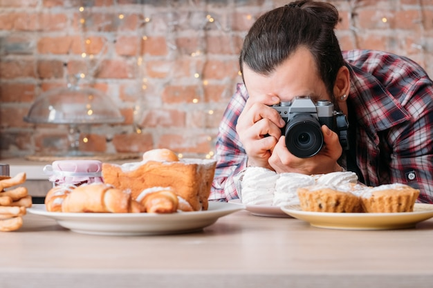 Fotografia kulinarna. asortyment deserów cukierniczych. mężczyzna z aparatem robiący zdjęcia talerza z bezą