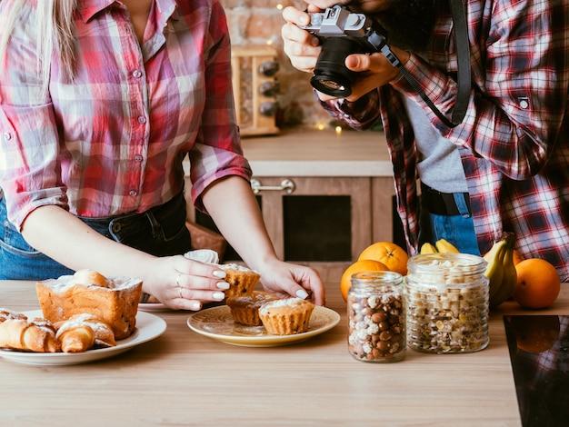 Fotografia kulinarna. słodka piekarnia. mężczyzna i kobieta biorąc zdjęcie domowych babeczek. świeże wypieki, słoiki z orzechami i owocami dookoła.