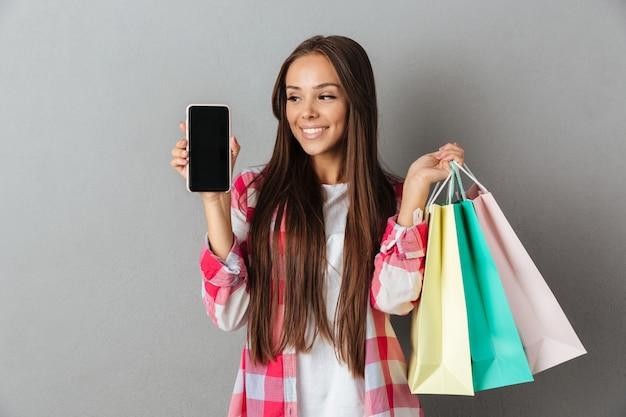 Fotografia ładnej kobiety mienia torba na zakupy, pokazuje pustego ekran mobilnego