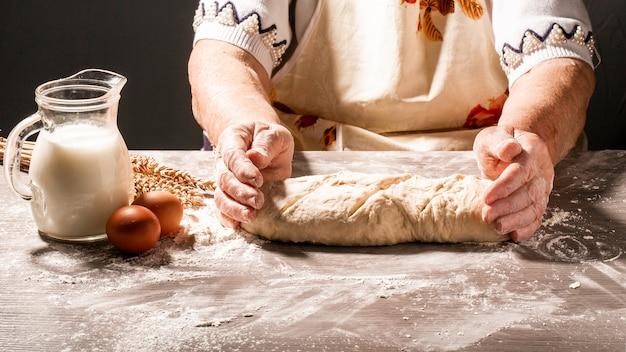 Fotografia mąki i kobiet ręki z mąki pluśnięciem. gotowanie chleba. ugniatanie ciasta. pojedynczo na ciemnym tle. puste miejsce na tekst