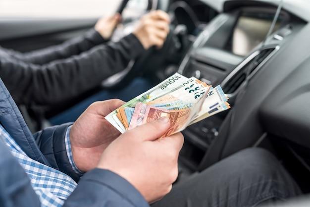 Fotografia makro męskich rąk trzymających banknoty euro