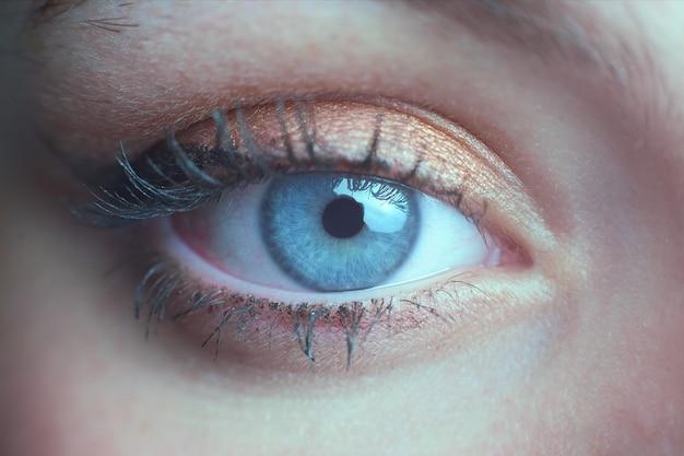 Fotografia makro pięknego niebiesko-zielonego oka kobiety z eyelinerem w kształcie skrzydła