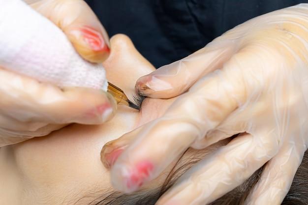 Fotografia makro procesu trwałego tatuowania powieki modelki