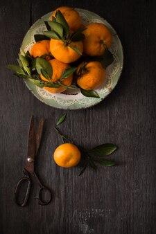 Fotografia martwa natura. ciemny nastrojowy obraz żywności świeżych dojrzałych owoców cytrusowych na drewnianym stole