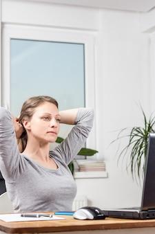 Fotografia młoda busienss kobieta rozciąga w domu biuro